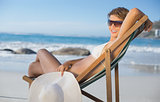 Pretty smiling woman relaxing in deck chair on the beach