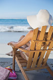 Woman in straw hat relaxing in deck chair on the beach