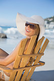 Smiling woman in straw hat relaxing in deck chair on the beach