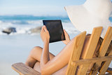 Woman in straw hat relaxing in deck chair on the beach using tablet pc