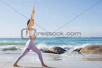 Sporty blonde stretching on the beach