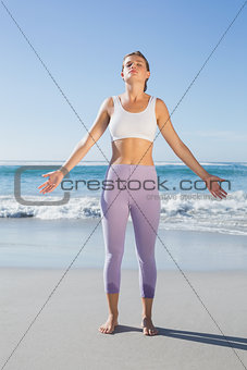 Sporty blonde standing on the beach with arms out