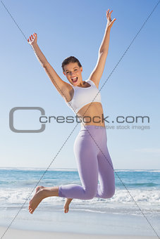 Sporty blonde jumping on the beach with arms out