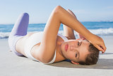Sporty blonde lying on the beach looking at camera