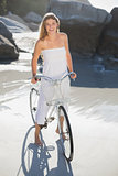 Beautiful blonde in white sundress standing with bike on the beach