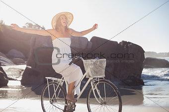 Beautiful blonde in white sundress on bike ride at the beach