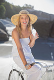 Beautiful blonde in sundress on bike holding water bottle at the beach