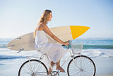 Beautiful surfer in sundress on bike holding surfboard at the beach