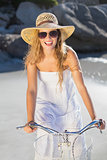 Beautiful smiling blonde in sundress on bike at the beach