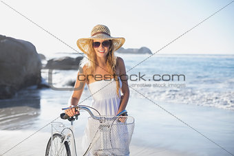Beautiful smiling blonde in sundress with her bike at the beach