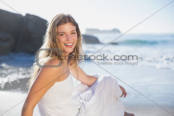 Beautiful smiling blonde in sundress sitting on the beach