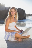 Beautiful smiling blonde in sundress using tablet on the beach