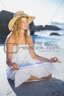 Beautiful blonde in sundress sitting in lotus pose on the beach