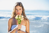 Beautiful blonde in sundress holding roses on the beach