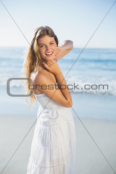 Beautiful blonde in white sundress on the beach