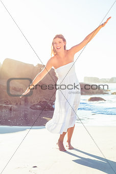 Beautiful happy blonde in white sundress on the beach