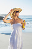 Beautiful blonde in white sundress on the beach with cocktail
