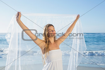 Beautiful calm blonde in white sundress on the beach with scarf