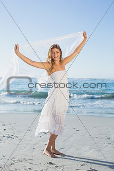 Beautiful happy blonde in white sundress on the beach with scarf
