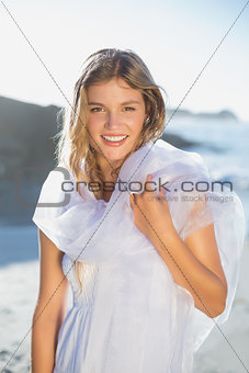 Beautiful smiling blonde in white sundress and scarf on the beach