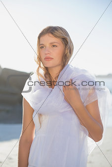 Beautiful blonde in white sundress and scarf on the beach