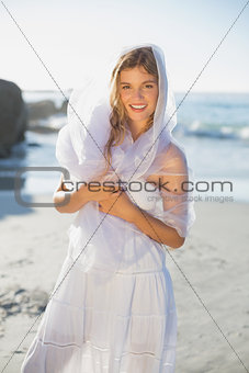 Beautiful happy blonde in white sundress and scarf on the beach
