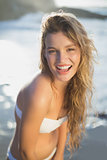 Beautiful smiling blonde in white bikini at the beach