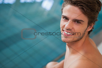 Fit swimmer smiling up at camera by the pool