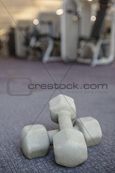 Grey dumbbells on the weights room floor