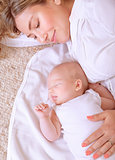 Newborn child sleeping with mom