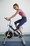 Fit woman on the spin bike smiling at camera