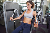 Fit woman using the weights machine for her arms
