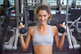 Fit smiling woman using the weights machine for her arms