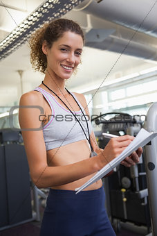 Fit trainer taking notes and smiling at camera