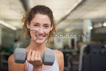 Fit woman smiling at camera lifting dumbbell