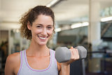 Fit woman smiling at camera lifting dumbbell