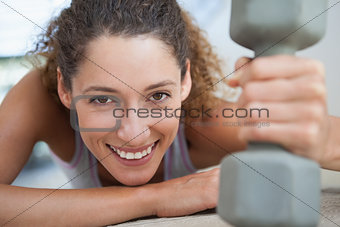 Fit woman smiling at camera holding dumbbell
