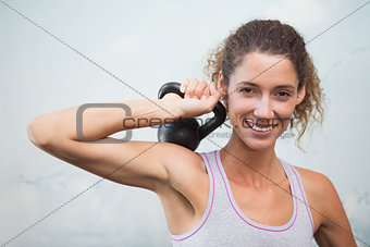 Fit woman smiling at camera holding kettlebell