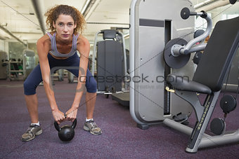 Fit woman squatting with kettlebell