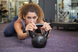 Fit woman lying with kettlebell