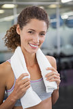 Fit woman smiling at camera with towel around shoulders