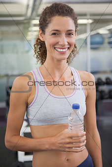 Fit woman smiling at camera holding water bottle