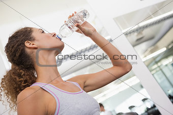 Fit woman drinking from water bottle