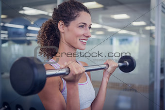 Fit smiling woman lifting barbell