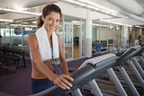 Fit woman wearing towel around shoulders on the treadmill