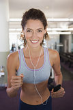 Fit smiling woman running on the treadmill