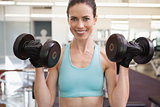 Smiling woman lifting heavy dumbbells