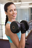 Smiling woman lifting heavy dumbbell
