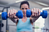 Smiling woman lifting blue dumbbells