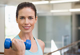 Smiling woman lifting blue dumbbell